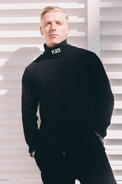 Camiseta LongFit Negra VLÄCK de hombre manga larga, con cuello alto ylogotipo bordado. Prenda de algodón orgánica, elegante y con estilo.